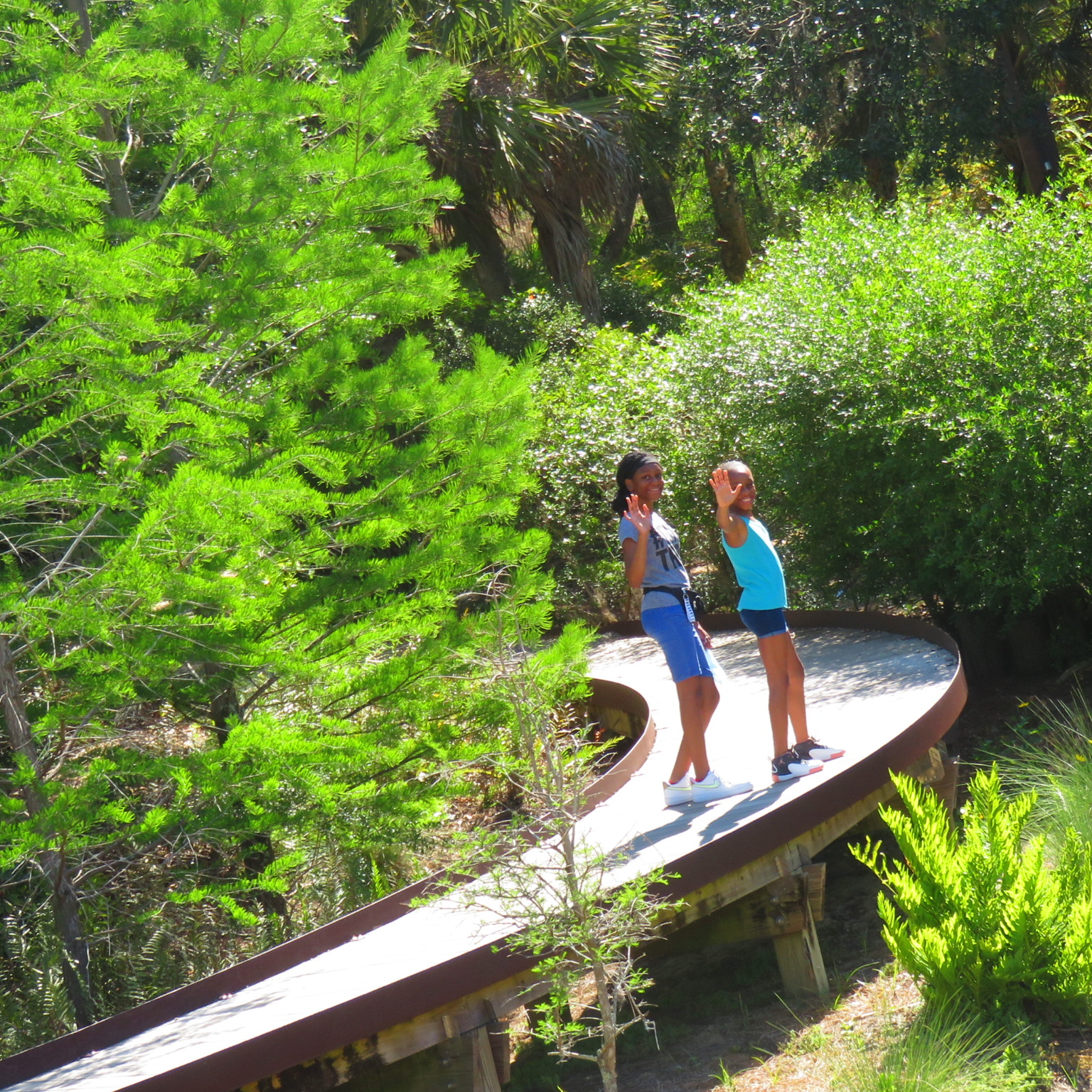 hiking trails at bok tower gardens, two young black girls smiling at the camera from the boardwalk