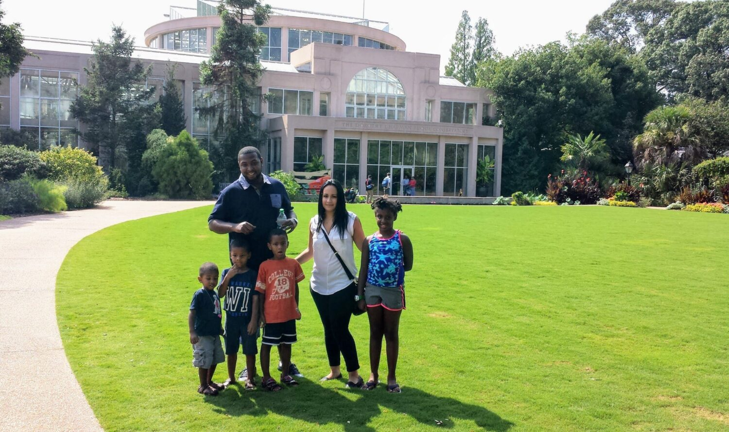 A family poses in front of the Atlanta Botanical Gardens, one of the best things to do in Atlanta with kids