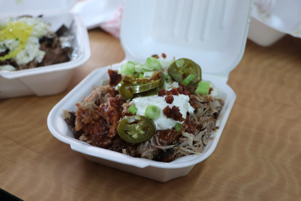 Styrofoam container filled with pulled pork, jalapenos, bacon, sour cream and barbecue sauce