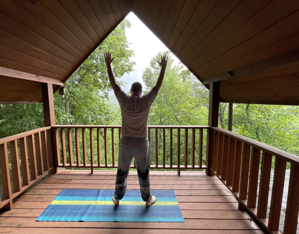 Man doing yoga on the deck of a log cabin at Little Valley Mountain Resort in Tennessee
