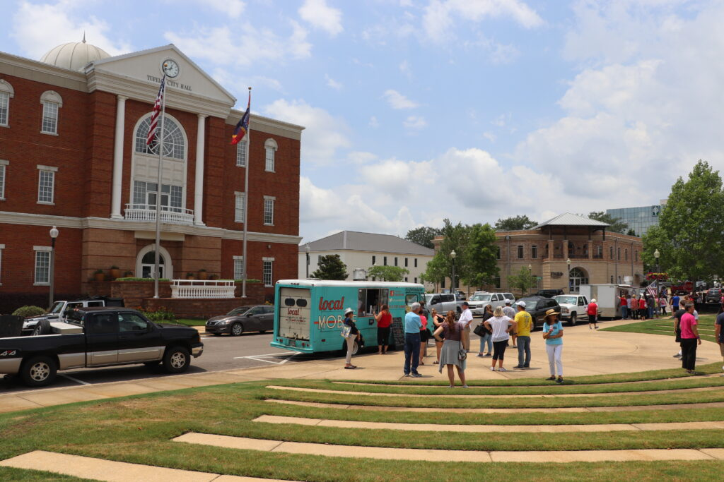 People gathered next to food trucks in Tupelo's Fairpark