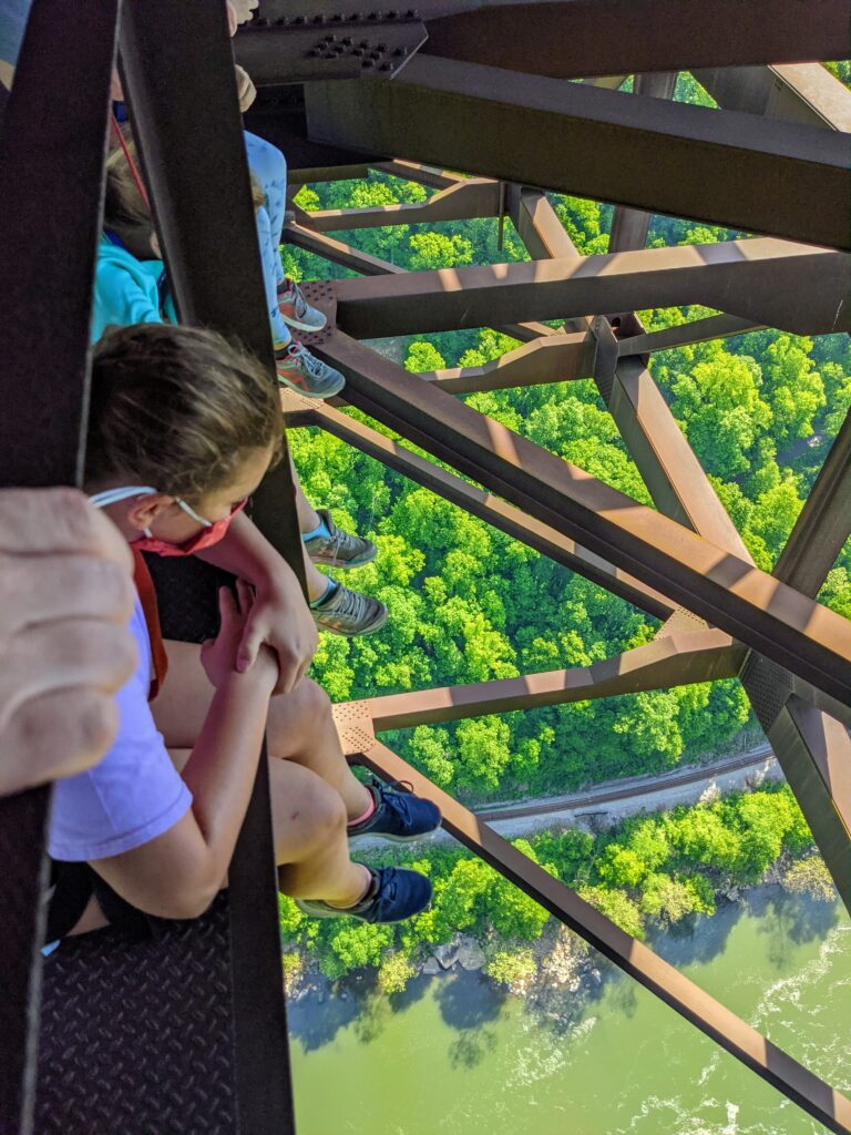 Girl sitting on the New River Bridge and looking down.