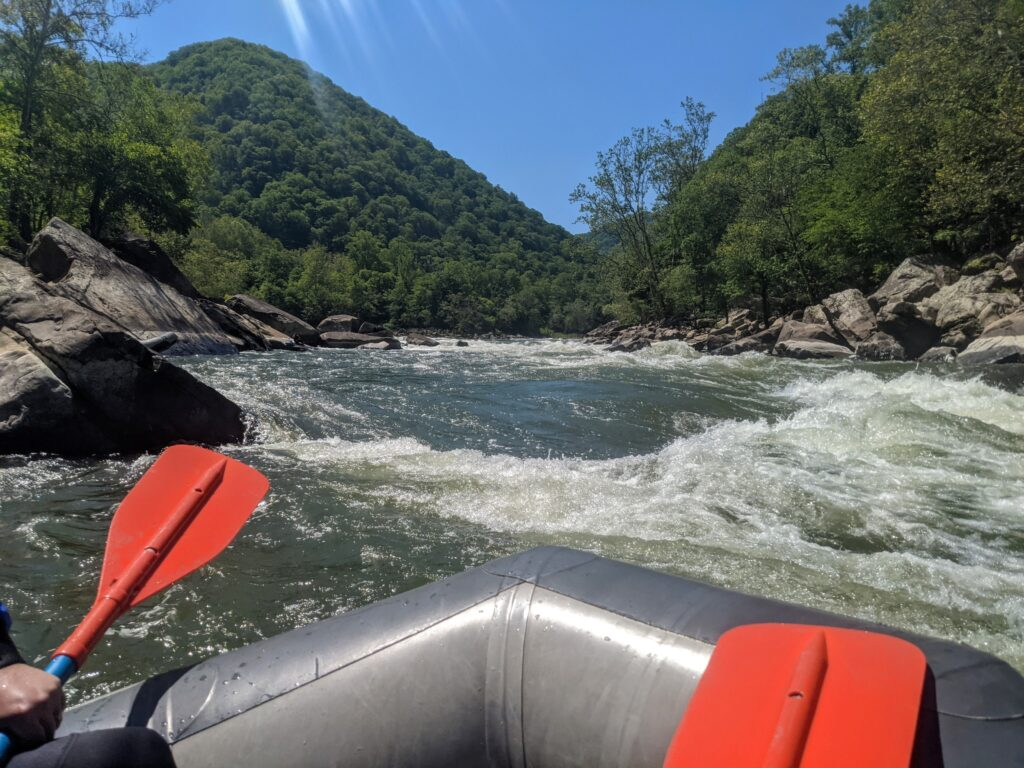 the bow of a whitewater raft heading into a rapid on the New River in West Virginia