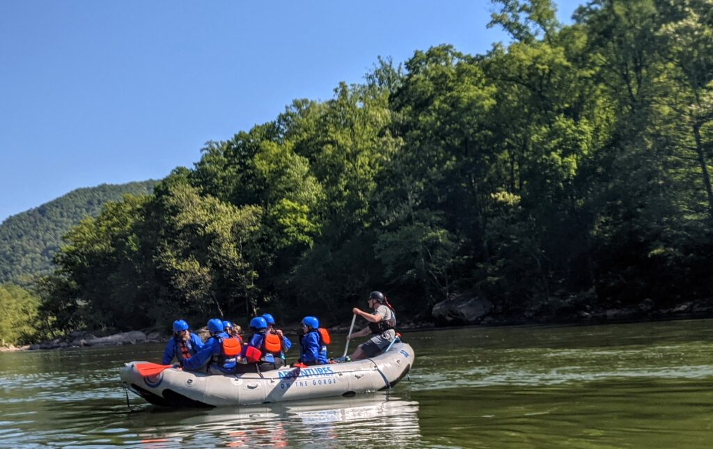 A whitewater raft filled with paddlers on the Upper New River.
