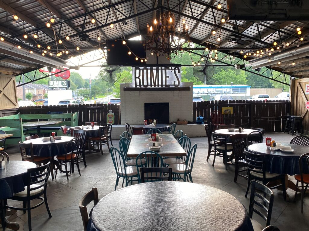 Covered outdoor patio strung with lights at Romie's Grocery