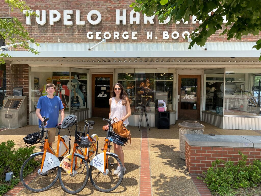 Woman and teen boy on bikes in front of Tupelo Hardware Co.