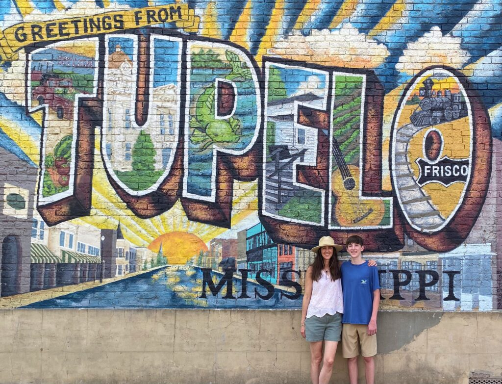 Woman and teen boy standing in front of the Greetings from Tupelo mural