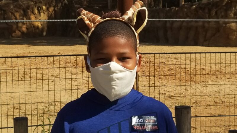 A boy with giraffe ears at Zoo Atlanta, one of the fun things to do in Atlanta for families