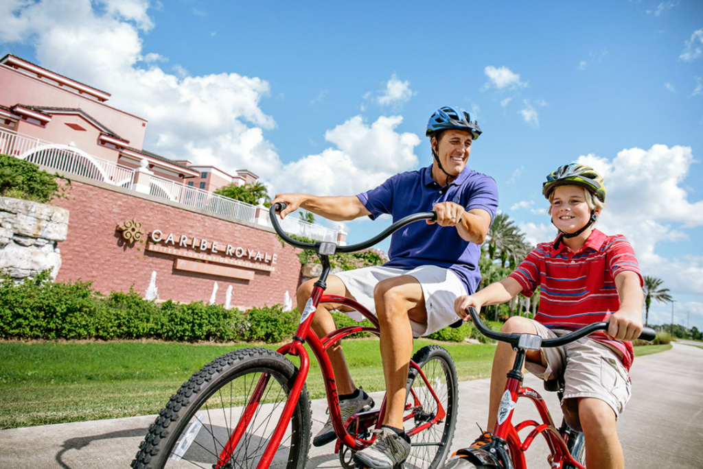 Man and boy riding bike outside the Caribe Royale All-Suite Hotel in Orlando, an off property Disney hotel