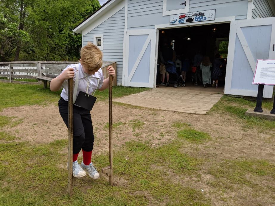 Young boy trying stilts at Crossroads Village in Flint, one of the top vacation spots in Michigan