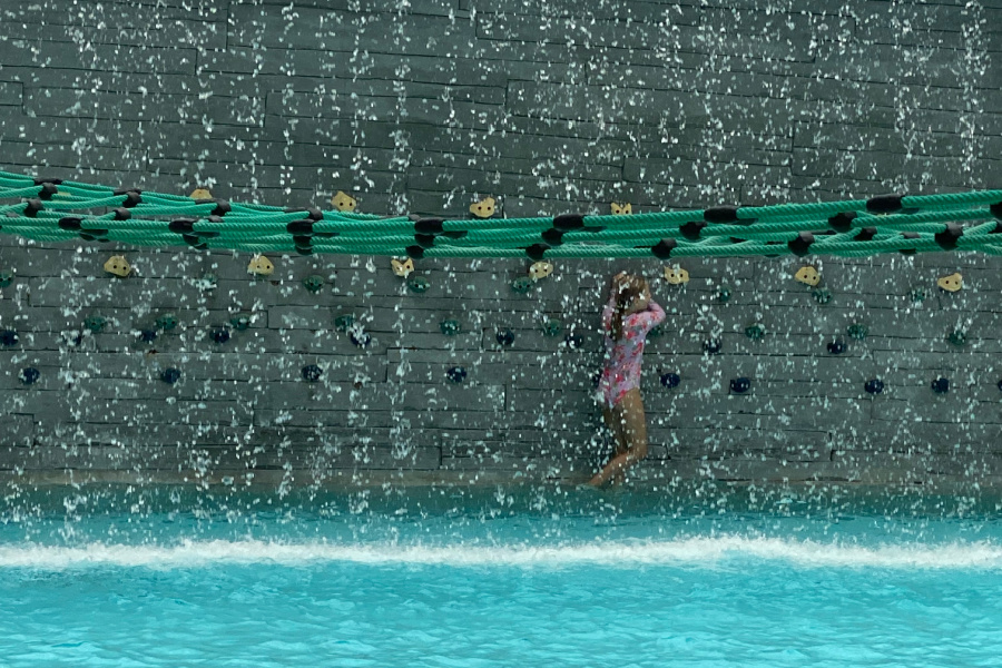 Young girl behind wall of water at Soundwaves in Nashville