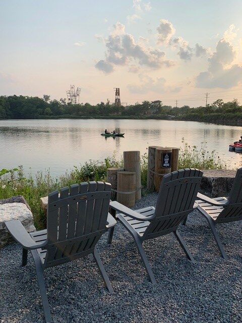 Chairs overlooking water at dusk at The Forge: Lemont Quarries