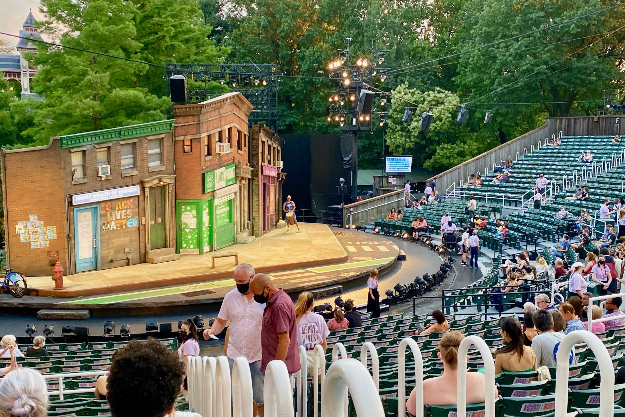 masked people looking for seats in Central Park's Delacorte Theater
