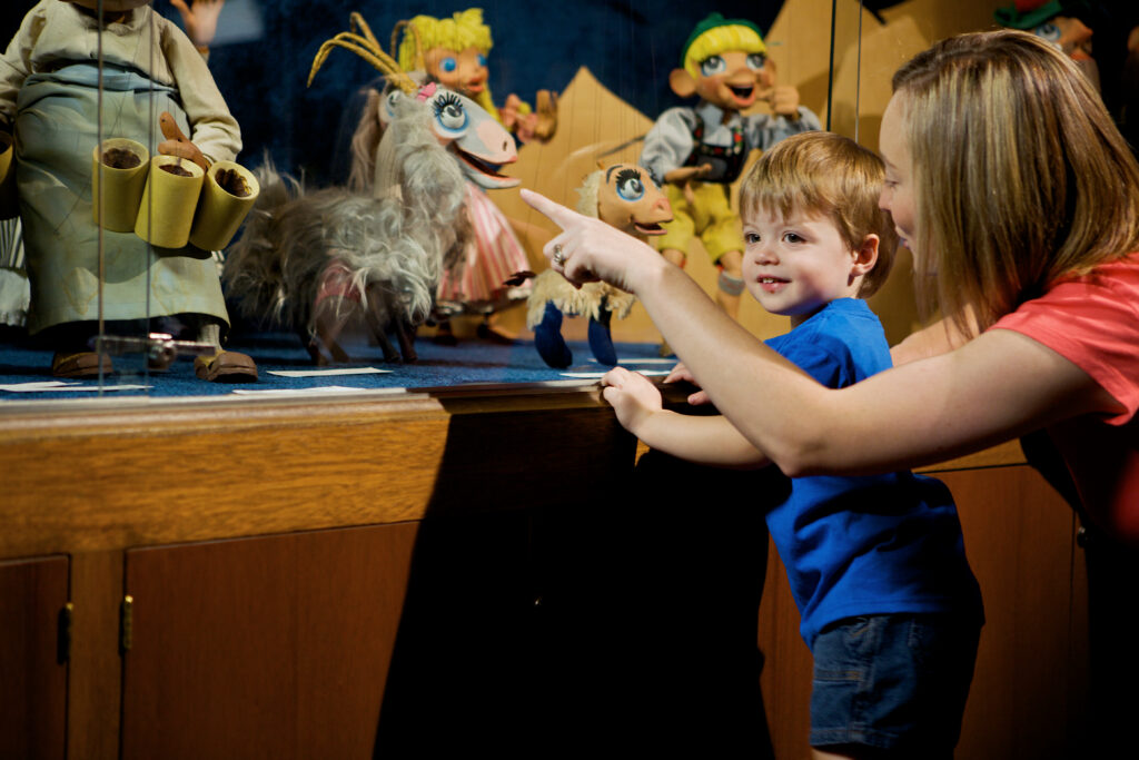 Mother and child looking at Bil Baird puppets, one of the things to do in mason city iowa