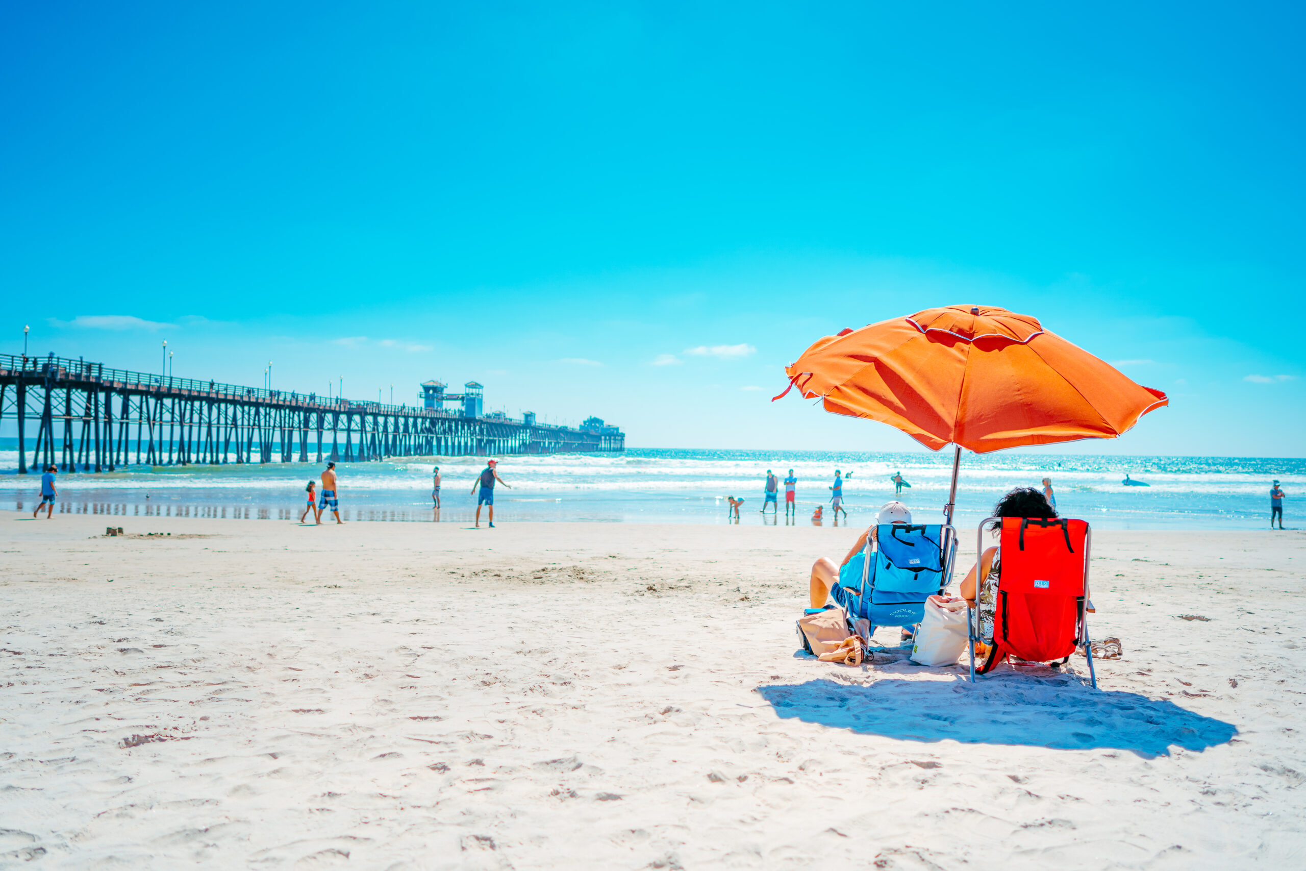 Couple with brightly colored beach chairs and umbrella enjoying the beach, one of the fun things to do in Oeanside CA