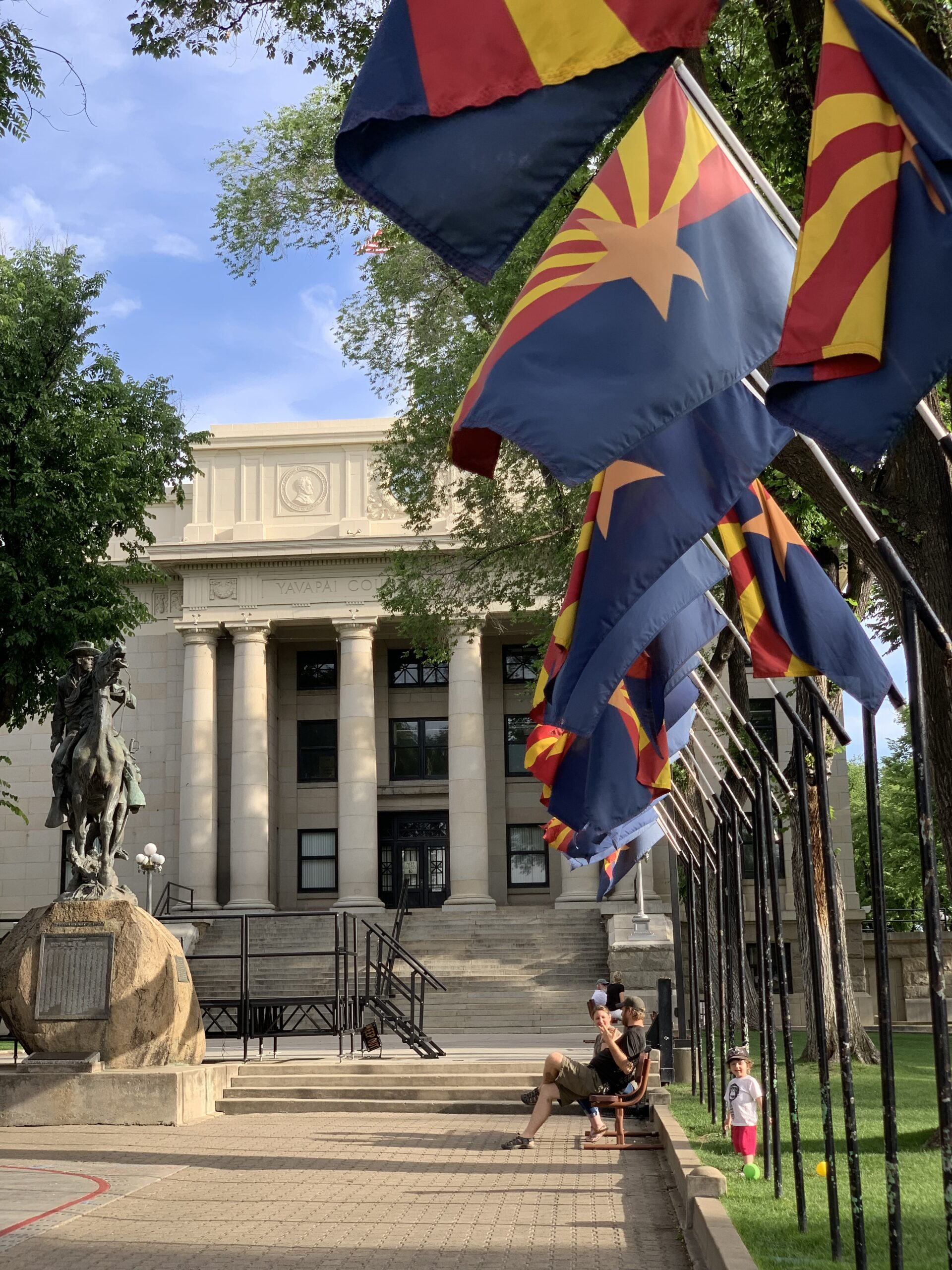 Things to do in Prescott AZ - Front of Courthouse at Courthouse Square with flags and statue