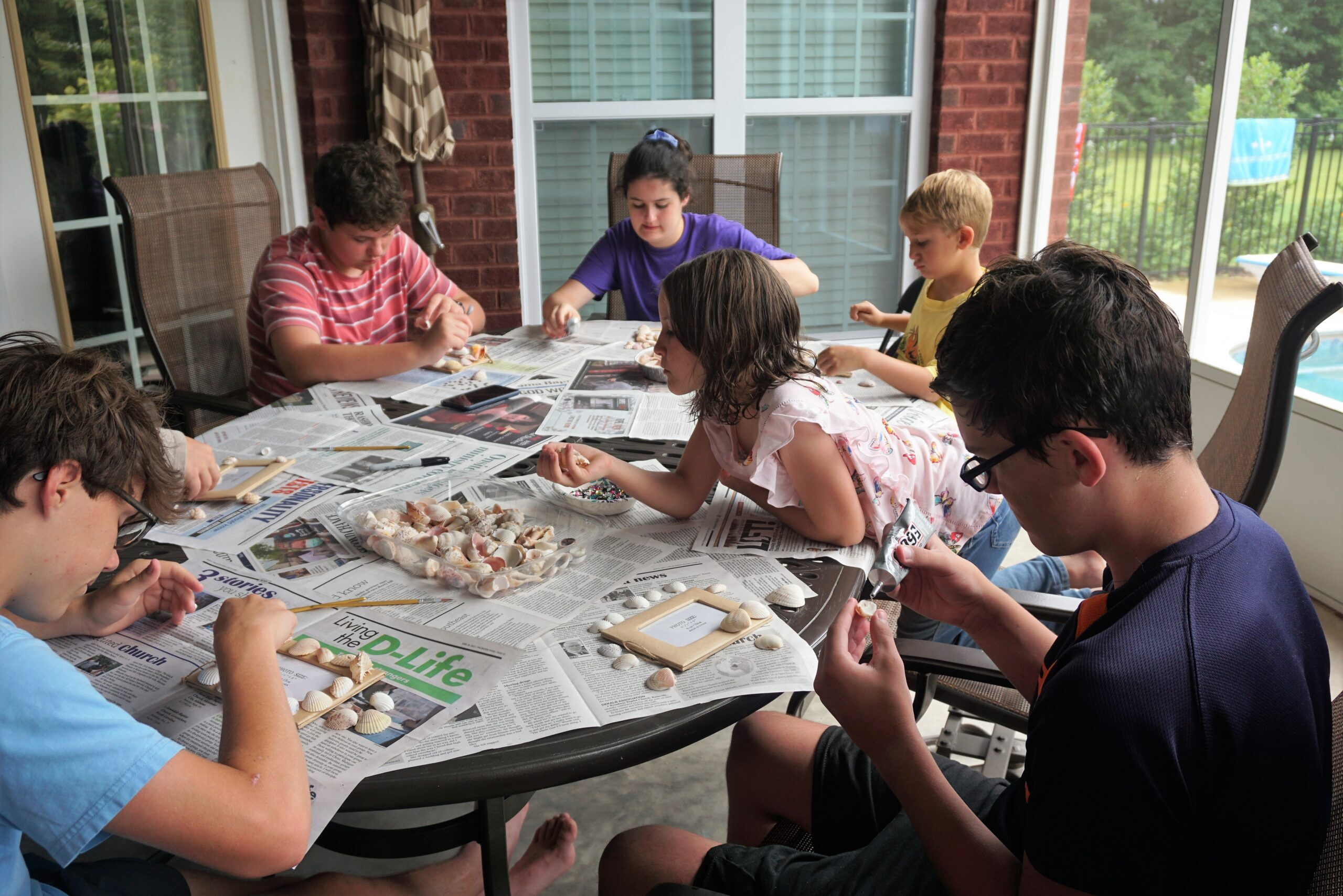 Cousin camp ideaa- Cousins doing a craft project with glue and shells.