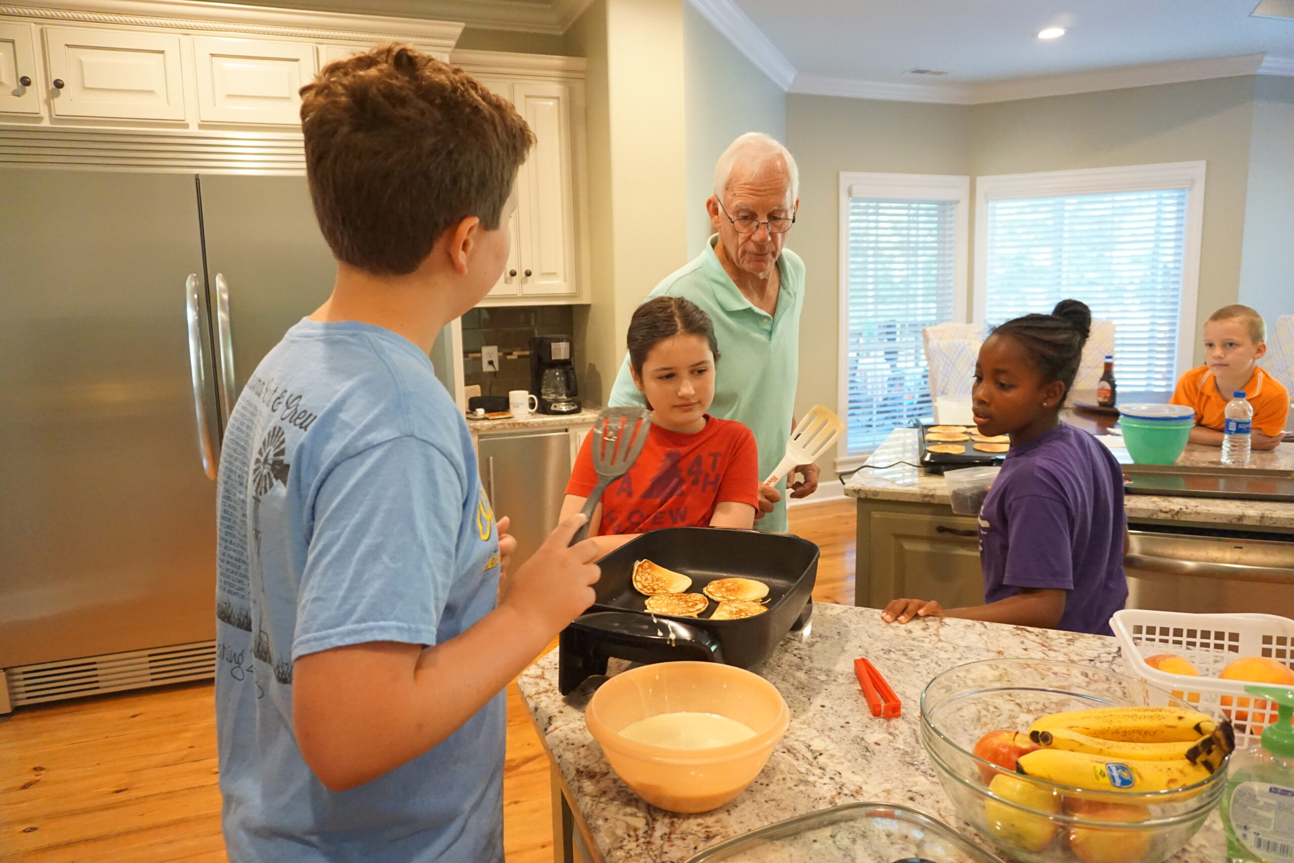 Cousin camp ideas - Cousins helping Granddaddy fix pancakes for breakfast