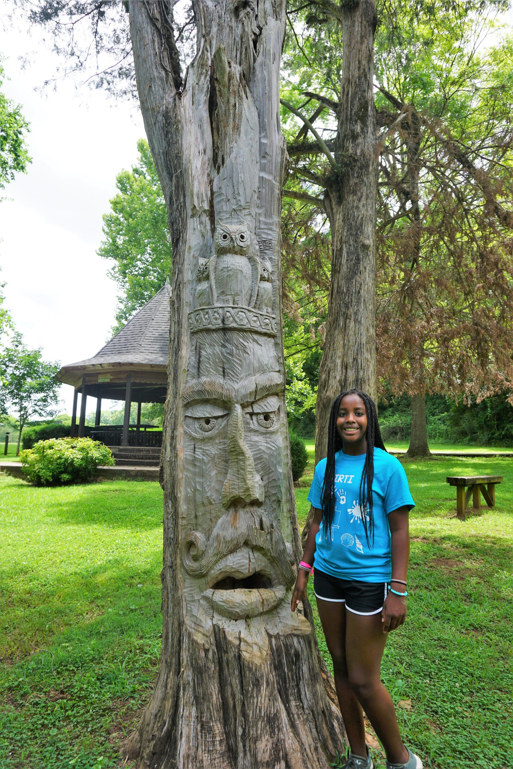 cousin camp ideas - cousin posing with an t.ree carving in a park