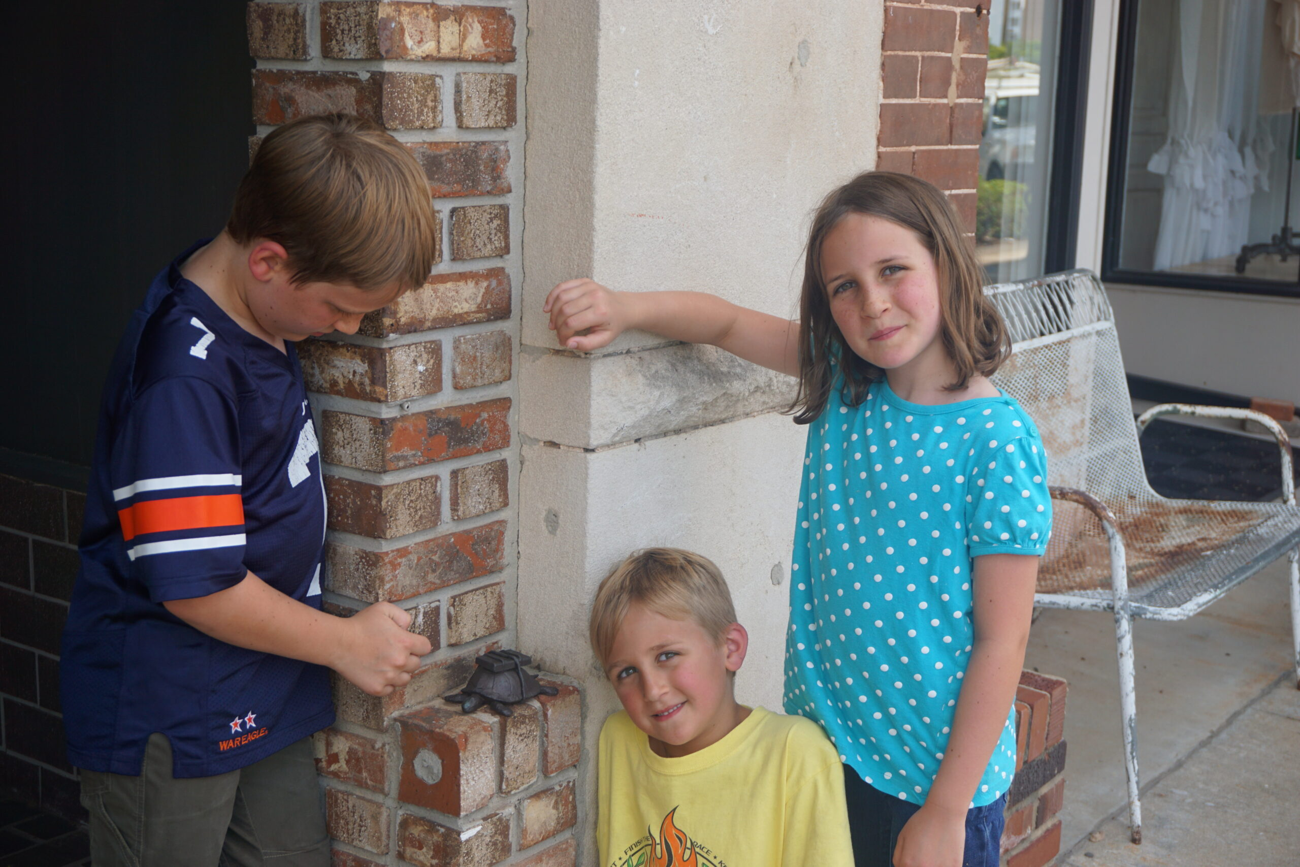 3 younger cousins with a bronze turtle found during a scavenger hunt.