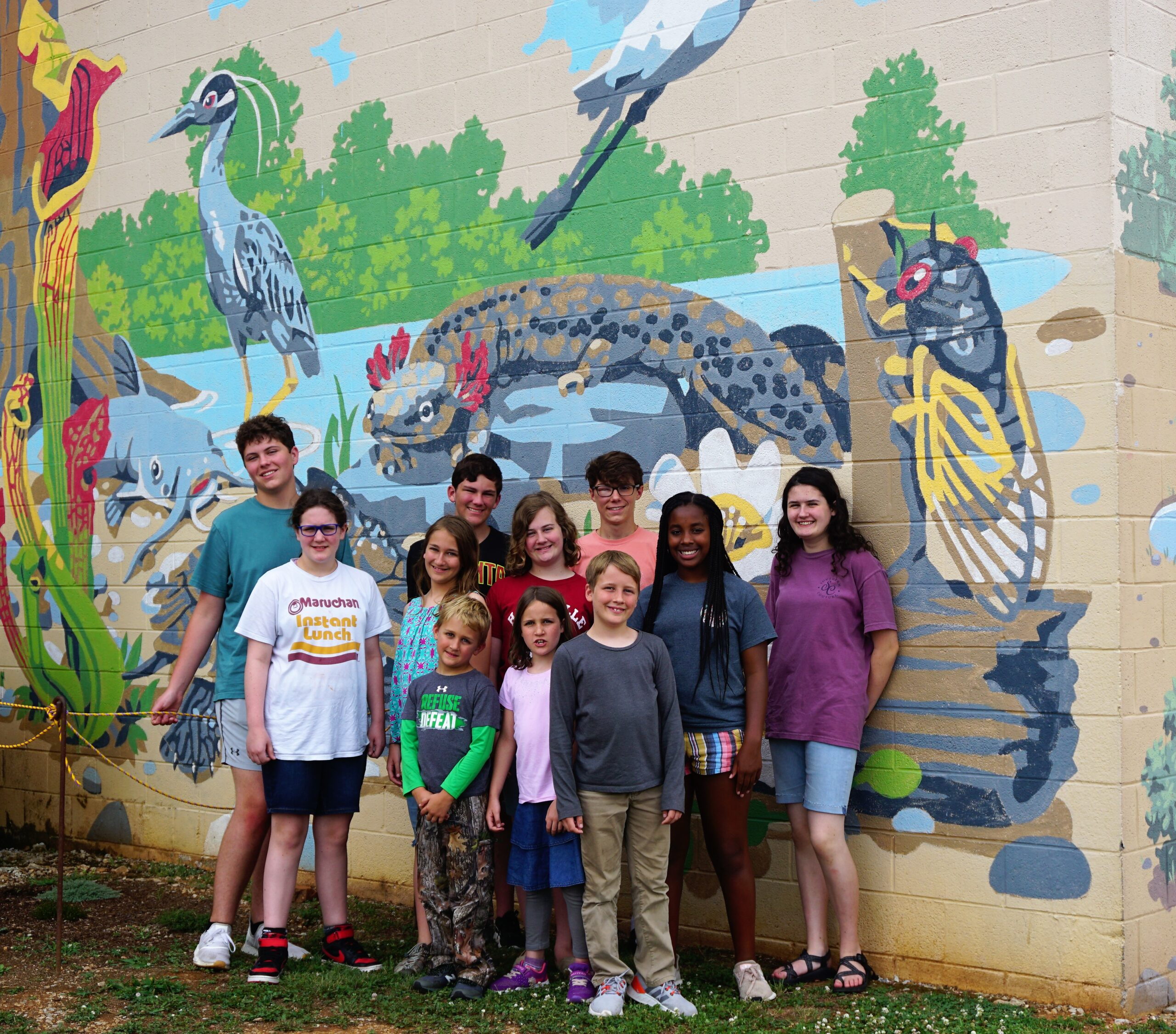 Photo of cousins in front of art mural at Lowe Mill in Huntsville during cousin camp.