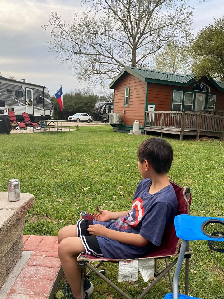 Boy glamping in Texas with cabin and Texas flag in the background