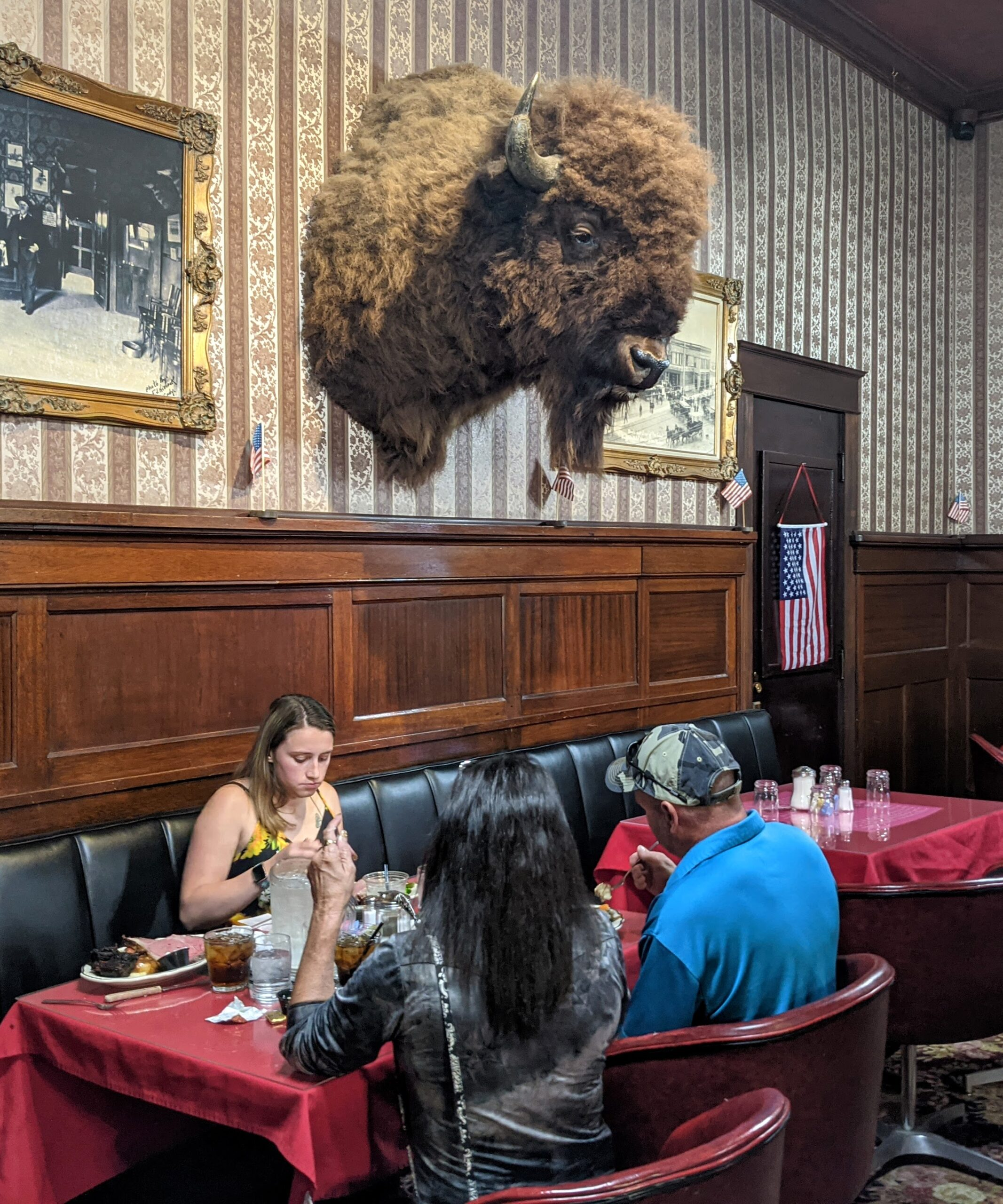 A bison head hangs over a table of people eating in The Irma Hotel in Cody Wyoming
