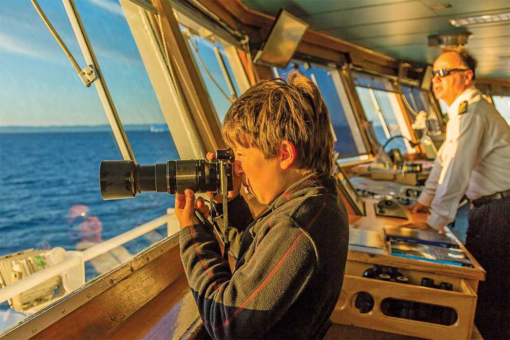 Lindblad cruise: Child with a camera on the bridge of the National Geographic Endurance.