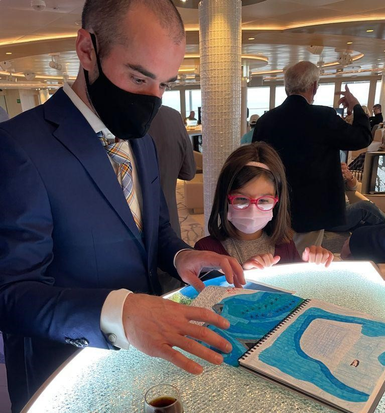 Lindblad cruise: Looking at drawings with the ship's naturalist.