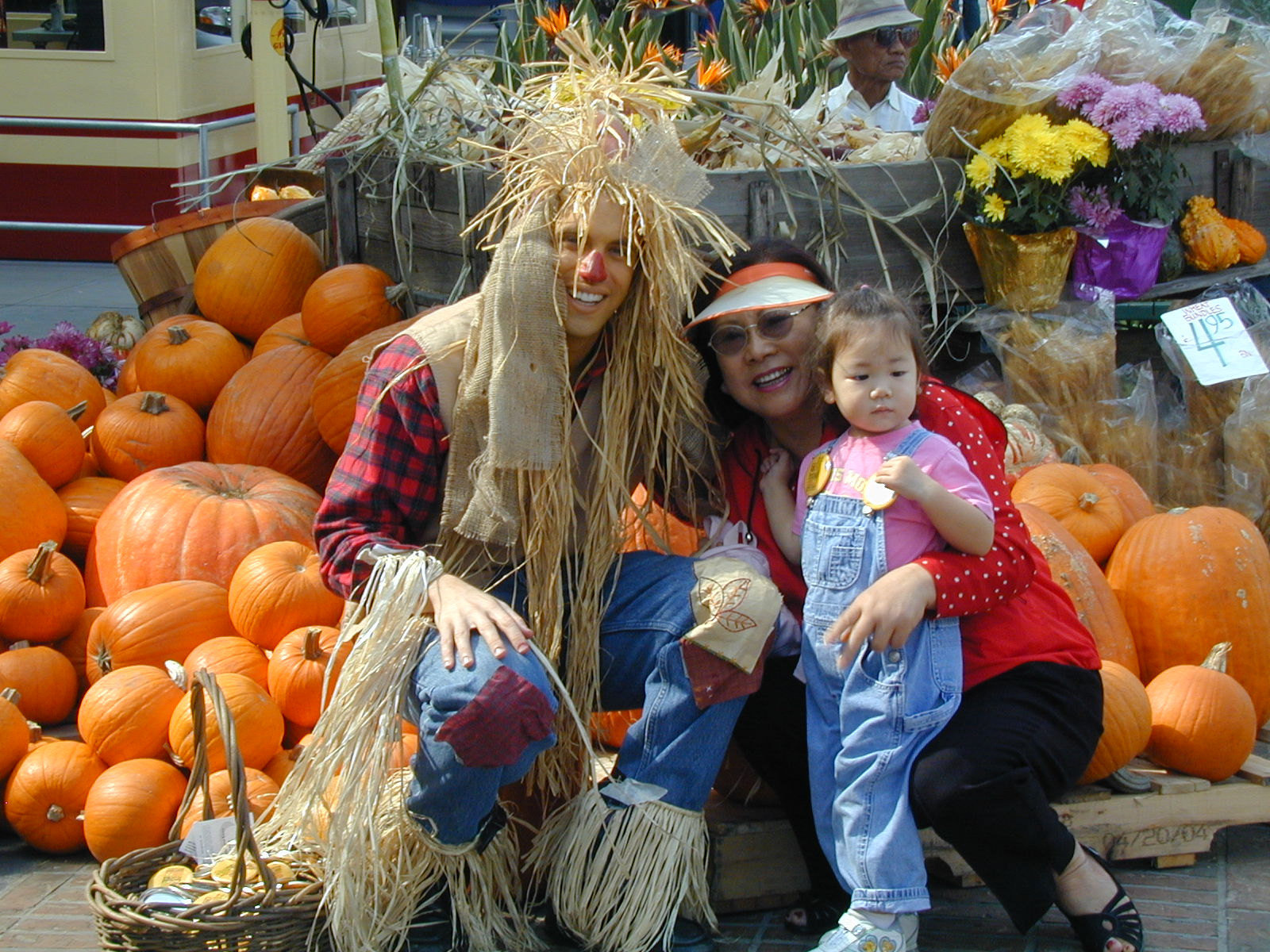 Woman, toddler and man dressed as scarecrow pose in front of pumpkins at the Original Farmers Market in LA