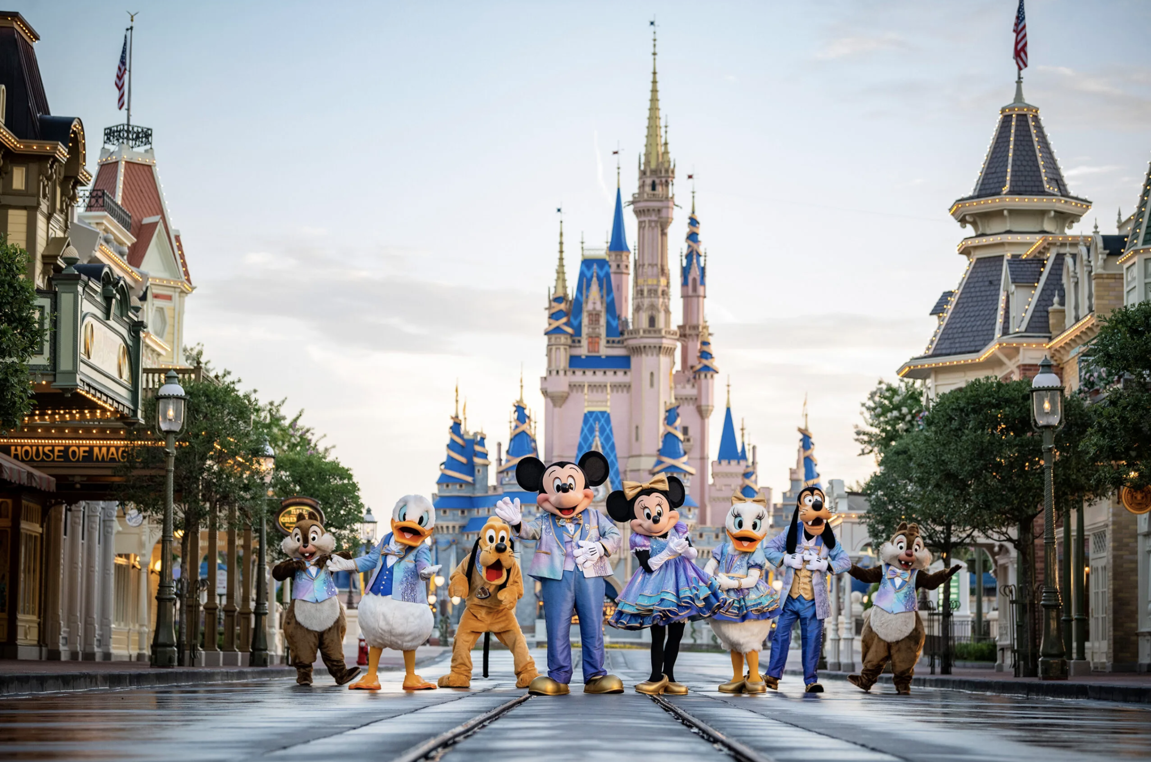 mickey and friends disney characters in their 50th anniversary sparkly EARidescence outfits in front of Cinderella Castle at Magic Kingdom