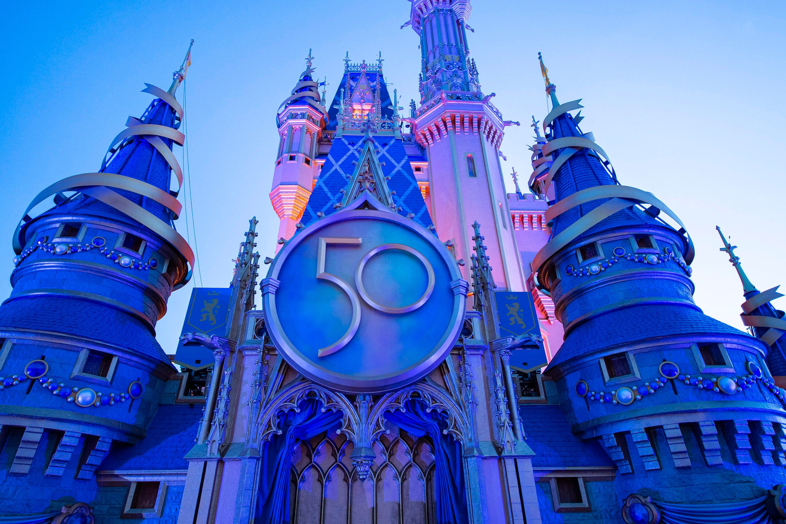 magic kingdom cinderella castle lit up at night with crest for 50th anniversary