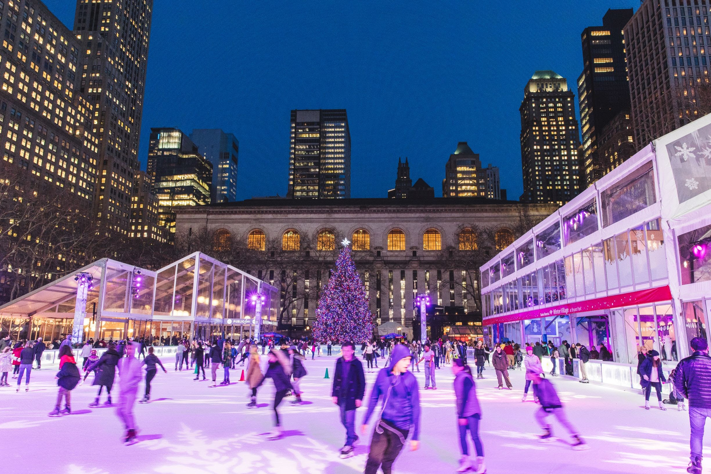 Ice skaters on the Winter Village rink in Bryant Park in the evening