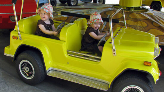 Twin toddlers enjoy a car ride at a local theme park, where no road trip games are required to keep them entertained!