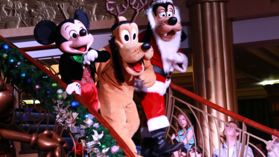 Mickey Mouse, Pluto, and Goofy are dressed in holiday attire to celebrate Christmas at Disney World