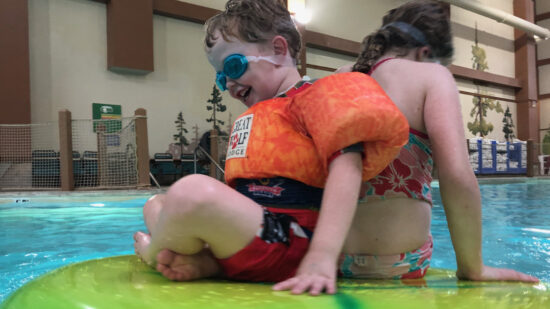 A preschooler in an orange puddle jumper and an older sibling play on a lily pad float in a Great Wolf Lodge pool