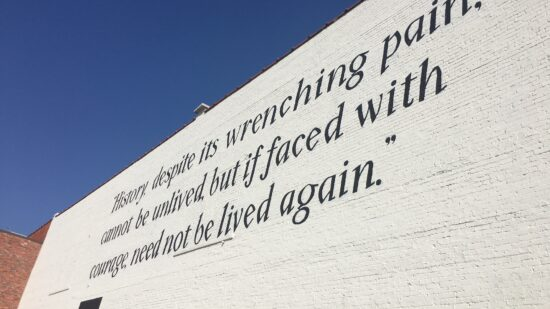 """white brick wall with black words reading """"History, despite its wrenching pain, cannot be unloved, but if faced with courage, need not be lived again."""" Maya Angelou - it's on the side of the Legacy Museum in Montgomery Alabama"""