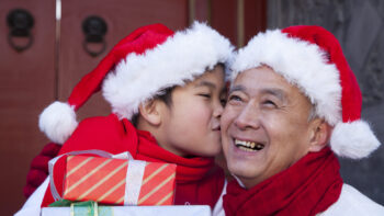 Grandfather and grandson holding gifts.