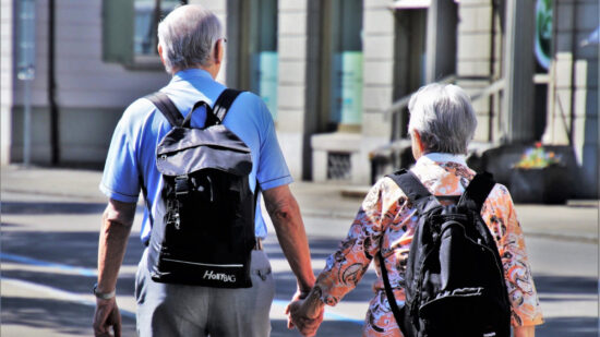 Two traveling seniors with backpacks