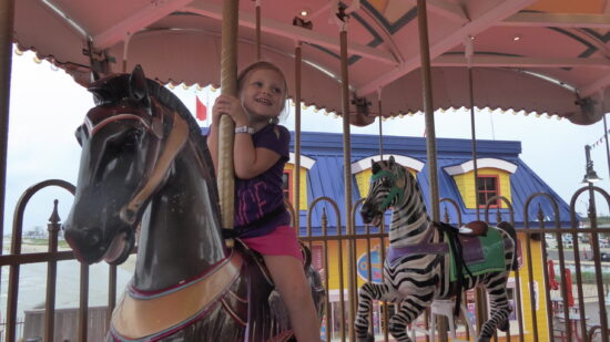 little blonde girl on a colorful carousel horse