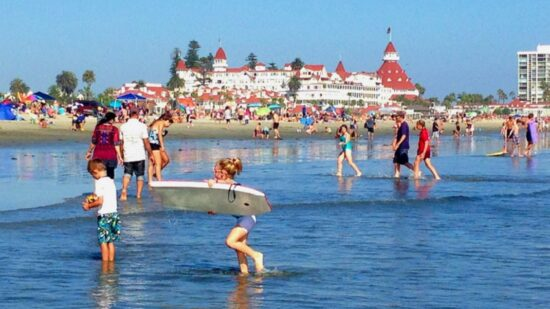 Hotel del Coronado shot from beach filled with families