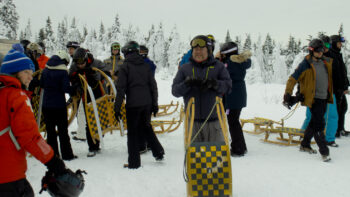 photo, a group of bundled up people holding and pulling sleds