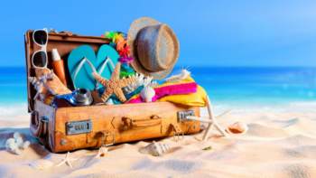 suitcase in the sand image for beaching packing list post