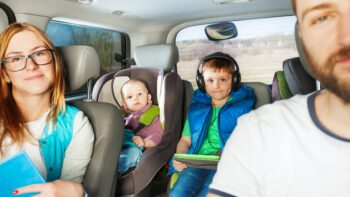 A caucasian family is in their car. The mother is wearing glasses and is holding a book. The focus is on a young boy in the back seat, middle. To his right is a young baby in a forward-facing carseat.