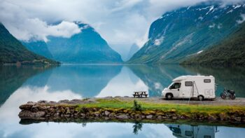 A perfectly calm fjord with an RV (recreational vehicle) and mopeds on a small peninsula in the foreground. The outdoor scene is very peaceful.