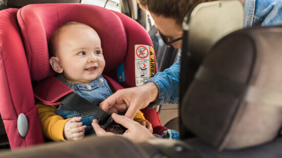 Mom buckling a baby into a car seat
