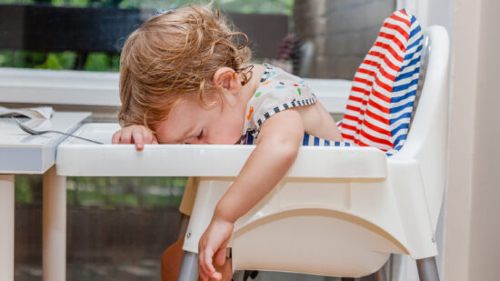 Tired toddler asleep in a high chair