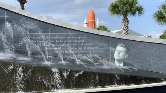 John F. Kennedy (JFK) Quote with fountain in foreground and space shuttle atlantis in background