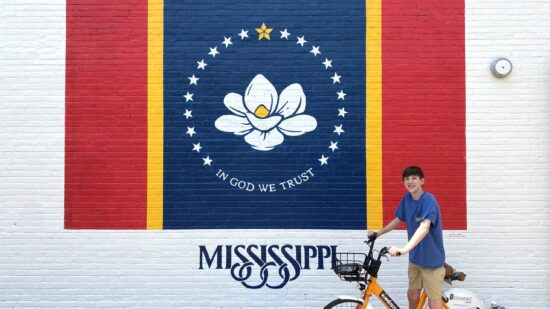 Teen boy on a bike in front of a Mississippi flag mural