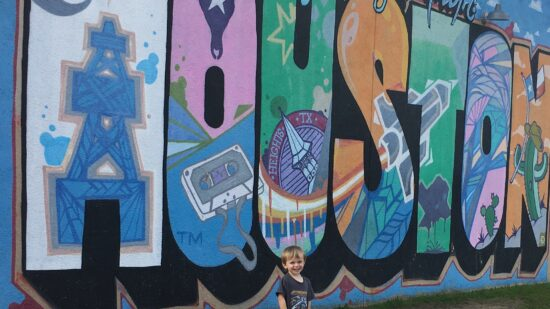 blonde toddler boy standing in front of colorful greetings from houston mural